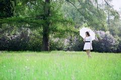 Girl with umbrella walking through a meadow Stock Photos
