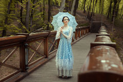 The girl with an umbrella. Woman standing on the bridge in a fantastic, magical forest. She is dressed in a vintage blue dress. In the hands holding an old Royalty Free Stock Photo