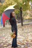 Girl with umbrella and yellow leaves. Girl and yellow leaves at autumn Royalty Free Stock Photos