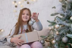 Girl under Christmas tree with ball Stock Images