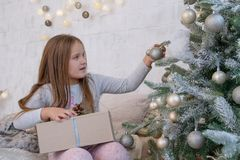 Girl under Christmas tree with ball Stock Image