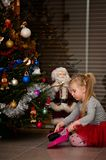Girl under Christmas tree cleaning needles Stock Photo