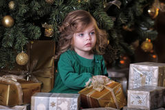 Girl  under the Christmas tree. The girl with a gift under the Christmas tree Stock Photo