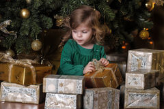 Girl  under the Christmas tree. The girl with a gift under the Christmas tree Royalty Free Stock Photography