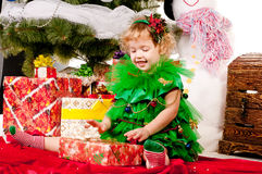A girl under the Christmas tree with gifts Stock Image
