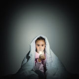 Girl under the covers with a flashlight Royalty Free Stock Photography
