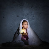 Girl under the covers with a flashlight Stock Photography