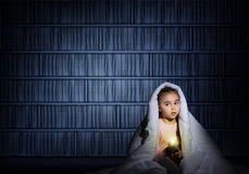 Girl under the covers with a flashlight Stock Photos
