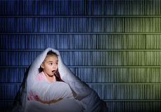 Girl under the covers with a flashlight Royalty Free Stock Photos