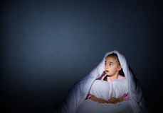 Girl under the covers with a flashlight Royalty Free Stock Images