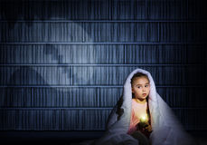 Girl under the covers with a flashlight Stock Image