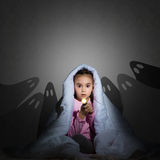 Girl under the covers with a flashlight Royalty Free Stock Image
