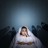 Girl under the covers with a flashlight Stock Photo