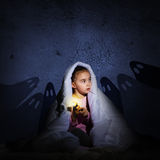 Girl under the covers with a flashlight Stock Images