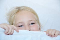 Girl under covers, looking at camera. High angle view Stock Photos