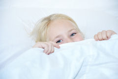 Girl under covers, looking at camera. Royalty Free Stock Photography