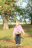 Girl under falling leaves Stock Photos