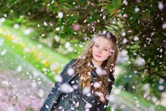 Girl under falling pink petals. On a spring day stock photography
