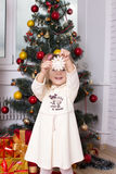 The girl under fir-tree holds a snowflake in hand Stock Photo