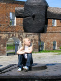 Girl under large hammer. In the park of historical engines Stock Photo