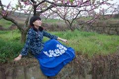 Girl under peach blossom Stock Photos