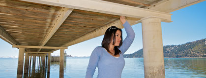 Girl under a pier at vacation resort Royalty Free Stock Photography