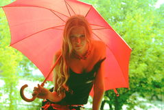 Girl under pink umbrella over green Stock Image