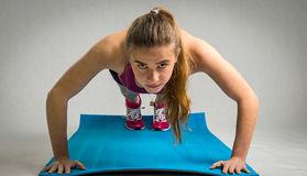 Girl under push ups training Royalty Free Stock Photography
