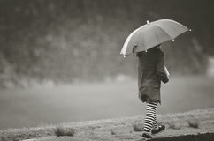 Girl under rain with umbrella. In black and white tone Stock Photos