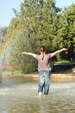 Girl under rainbow Stock Photo