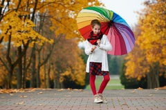 Girl under rainbow umbrella in autumn park Stock Photos