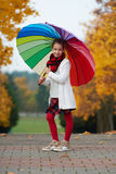 Girl under rainbow umbrella in autumn park Royalty Free Stock Photo