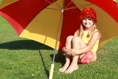 Girl under the red and yellow umbrella. Barefoot little girl in red and yellow dress sitting under a red and yellow umbrella Stock Images