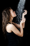 The girl under a shower on the black Stock Photos