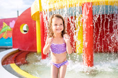 Girl under splashing fountain. Summer heat and water. Stock Photography