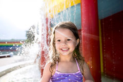 Girl under splashing fountain. Summer heat and water. Cute little girl in swimsuit having fun under splashing fountain, smiling. Summer heat and water Royalty Free Stock Photo