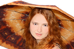 Girl under umbrella. Beautiful red-haired girl under brown umbrella Royalty Free Stock Photography