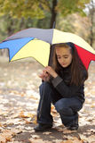 Girl under umbrella. Girl and yellow leaves at autumn Stock Image
