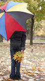 Girl under umbrella. And yellow leaves at autumn Stock Photos