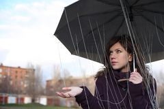 The girl under an umbrella. Catches rain drops. A rain from threads stock photo