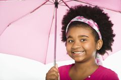 Girl under umbrella. African American girl holding pink umbrella smiling at viewer Royalty Free Stock Image