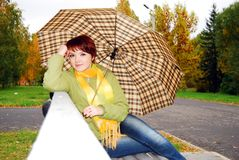 Girl under an umbrella on an old bench. Stock Image