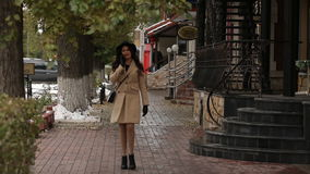 Girl under umbrella walking and talking on the phone. Girl in a beige coat under umbrella walking and talking on the phone stock video footage