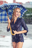 Girl under umbrella watching the rain Stock Image