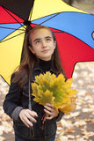 Girl under umbrella with yellow leaves. Girl and yellow leaves at autumn. Under umbrella Stock Photo