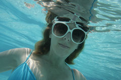 Girl Under Water. Young girl wearing sun glasses under water in swimming pool Royalty Free Stock Images