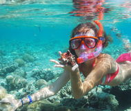 Girl under water. A girl in the mask of diver holds a cockleshell under water Stock Image
