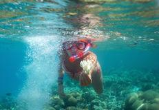 Girl under water. A girl in a diving mask floats under water shows punished Stock Photos