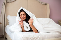 Girl under white blanket. Smiling woman indoor. Find a perfect hiding spot Royalty Free Stock Image