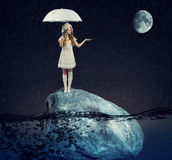 girl  under a white umbrella on a large rock Royalty Free Stock Photography